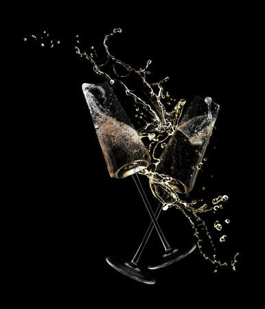 Glasses of champagne clinking together and splashing on black background