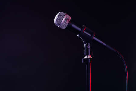 Modern microphone on stand against black background. Space for text Banco de Imagens