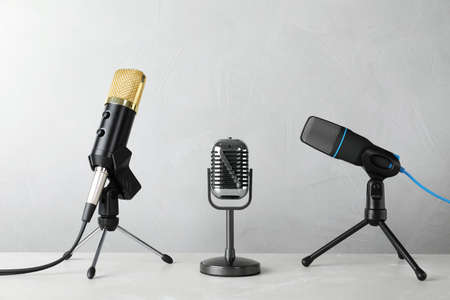 Different microphones on table against grey background