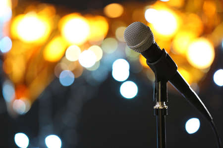 Microphone against festive lights, space for text. Musical equipment Banque d'images - 119679412