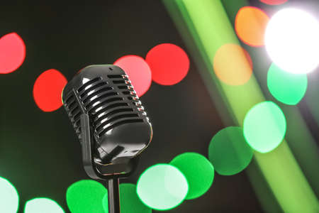 Retro microphone against festive lights, space for text. Musical equipment Banque d'images - 119679459