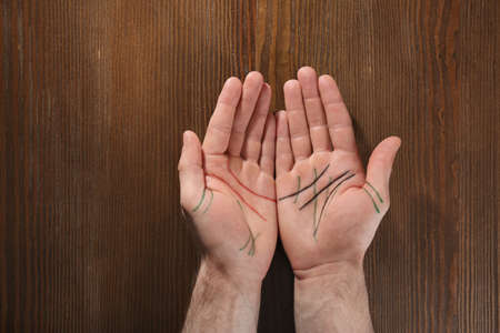 Man showing palms with drawn lines on wooden background, top view. Chiromancy and foretelling