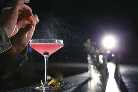 Barman making cosmopolitan martini cocktail at counter, closeup. Space for text
