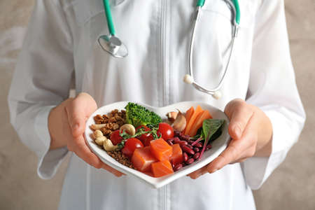 Doctor holding plate with products for heart-healthy diet, closeup