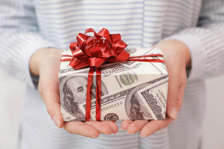 Woman holding gift box wrapped in dollars, closeup