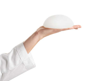Doctor holding silicone implant for breast augmentation on white background. Cosmetic surgery Stock Photo