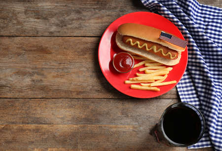 Tasty hot dog, French fries and drink on wooden background, top view with space for text. Traditional American food Stock Photo