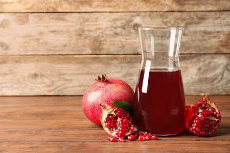 Jug of pomegranate juice and fresh fruits on table against wooden background, space for text