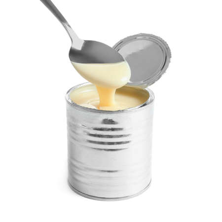 Condensed milk pouring from spoon into tin can on white background. Dairy product