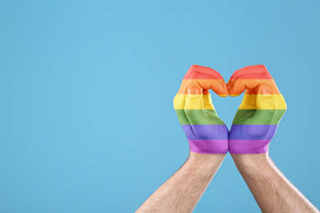 Man making heart with hands painted in LGBT flag on color background, closeup and space for text. Gay community