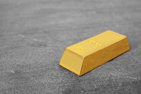 Shiny gold bar on table. Space for text Stock Photo