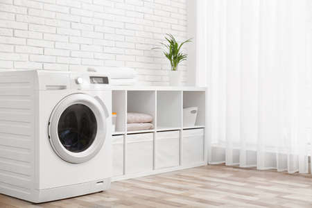 Modern washing machine near brick wall in laundry room interior, space for text Reklamní fotografie - 120157627
