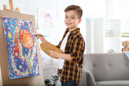Cute little child painting on easel at home Stock Photo