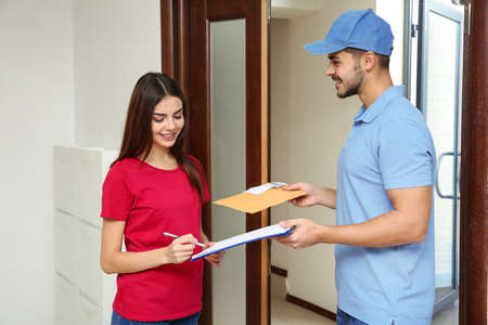 Woman receiving padded envelope from delivery service courier indoors