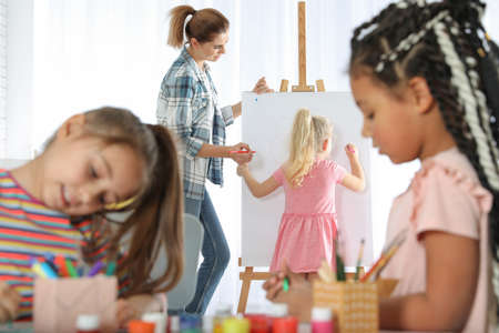 Female teacher with child near easel at painting lesson indoors Фото со стока