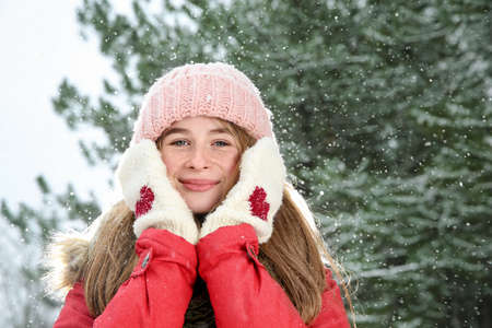 Portrait of teenage girl in winter snowy forest