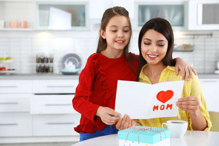 Daughter congratulating her mom in kitchen, space for text. Happy Mother's Day