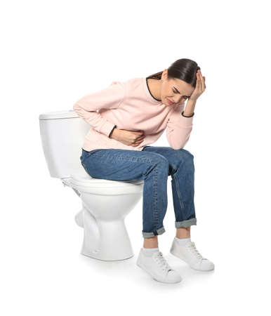 Young woman suffering from digestive disorder on toilet bowl, white background