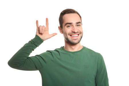 Man showing I LOVE YOU gesture in sign language on white background Standard-Bild