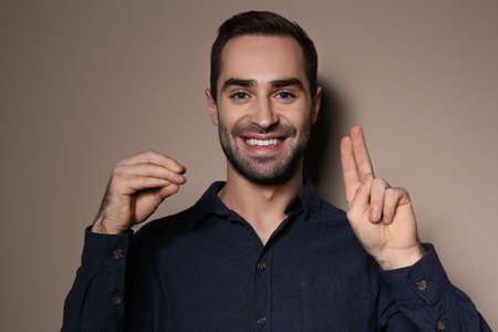 Hombre usando lenguaje de señas sobre fondo de color Foto de archivo