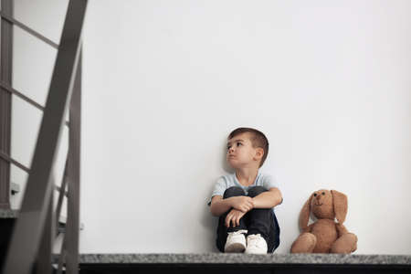 Sad little boy with toy sitting near white wall