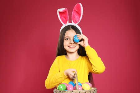 Kleines Mädchen mit Hasenohren-Stirnband, das Korb mit Ostereiern auf farbigem Hintergrund hält