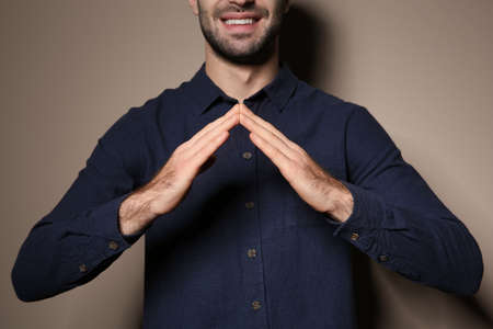 Man showing HOUSE gesture in sign language on color background, closeup
