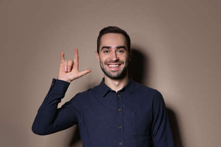 Man showing I LOVE YOU gesture in sign language on color background Stock Photo