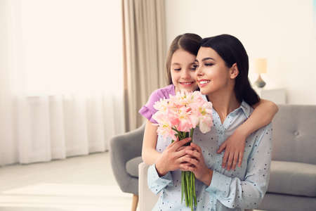 Little daughter congratulating her mom at home, space for text. Happy Mothers Day