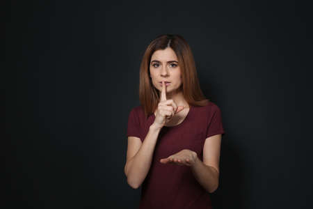 Woman showing HUSH gesture in sign language on black background Imagens