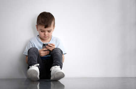 Sad little boy with mobile phone sitting near white wall, space for text