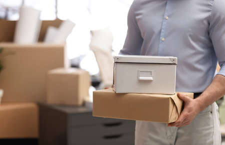 Man holding moving boxes in new office, closeup. Space for text Stock Photo