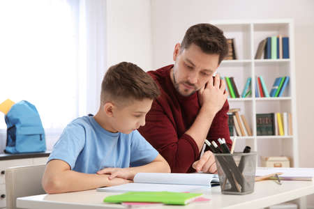 Dad helping his son with homework in room Imagens