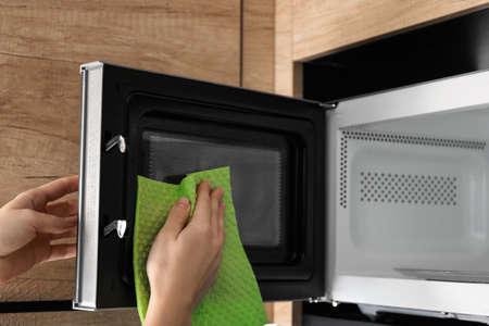 Mujer limpieza horno microondas con un trapo en la cocina, primer plano Foto de archivo