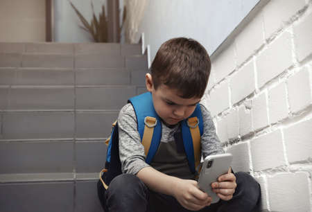 Sad little boy with mobile phone sitting on stairs indoors
