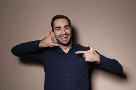Man showing CALL ME gesture in sign language on color background