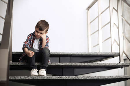 Sad little boy sitting on stairs indoors