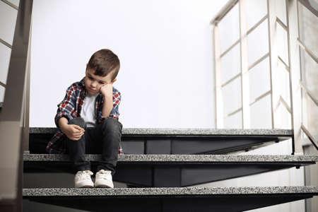 Triste petit garçon assis dans les escaliers à l'intérieur