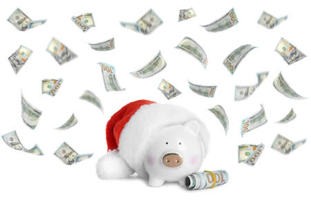 Cute piggy bank in Santa hat and flying American dollars on white background