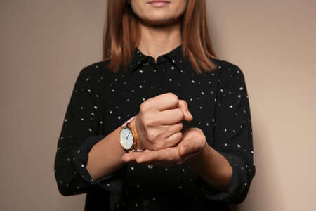Woman showing word CRUCIFY in sign language on color background, closeup