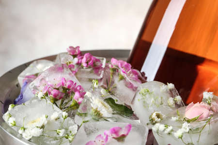 Floral ice cubes and bottle of champagne in bucket, closeup