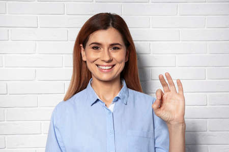 Woman showing OK gesture in sign language near brick wall Stock Photo