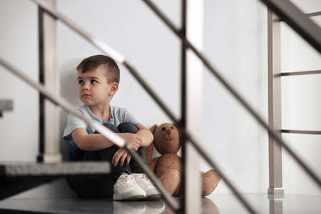 Sad little boy with toy sitting indoors 版權商用圖片