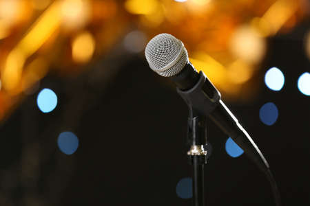 Microphone against festive lights, space for text. Musical equipment