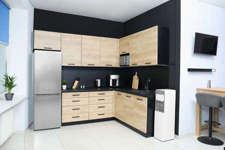 Acogedor interior de cocina moderna con muebles y electrodomésticos nuevos