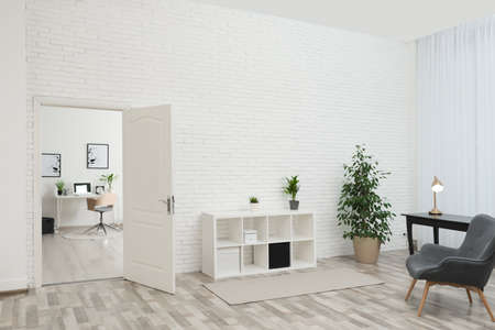 Living room interior with stylish furniture and open door