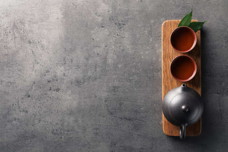 Board with cups and teapot of freshly brewed oolong on grey background, top view with space for text Reklamní fotografie