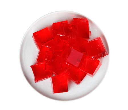 Plate with red jelly cubes on white background, top view