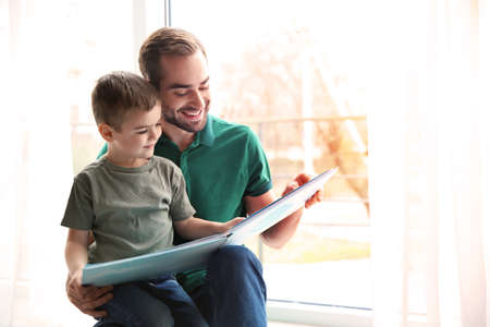 Father and his little son reading book near window at home, space for text Stok Fotoğraf