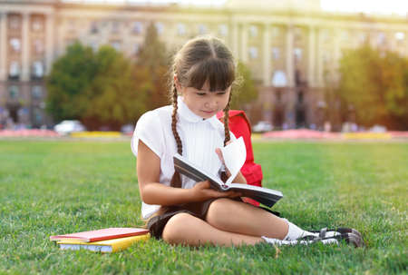 Cute little schoolgirl sitting on green grass and reading book outdoors